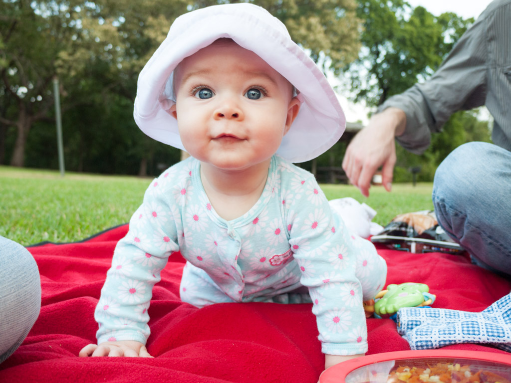 Bridget on a picnic blanket wearing a sun hat.